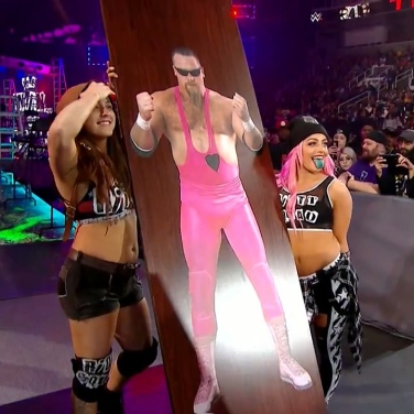 Sarah Logan and Liv Morgan help their Riott Squad sister, Ruby Riott, by taunting Natalya witha table featuring the image of her late father
