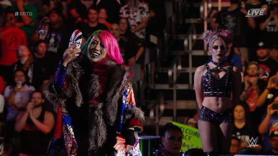 Asuka, ready to battle for the MITB briefcase, with Alexa Bliss lurking in the shadows.